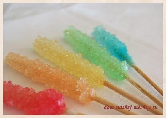 Налить сахарный сироп в стеклянные баночки или стаканы, добавить пищевые красители. Медленно опустить палочки в раствор и закрепить прищепками. Обратите внимание, чтобы палочки не касались ни дна банки, ни друг друга, между ними должно остаться расстояние, для обрастания кристаллами.